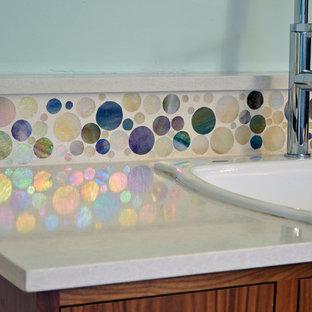 シアトルの中サイズのミッドセンチュリースタイルのおしゃれなキッチン (ドロップインシンク、フラットパネル扉のキャビネット、中間色木目調キャビネット、クオーツストーンカウンター、マルチカラーのキッチンパネル、ガラスタイルのキッチンパネル、シルバーの調理設備の、磁器タイルの床) の写真
