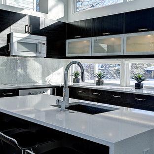 Imagen de cocina en L, contemporánea, de tamaño medio, abierta, con fregadero bajoencimera, armarios tipo vitrina, encimera de cuarzo compacto, electrodomésticos blancos, una isla, puertas de armario negras, salpicadero blanco, salpicadero de azulejos de vidrio y suelo de madera clara
