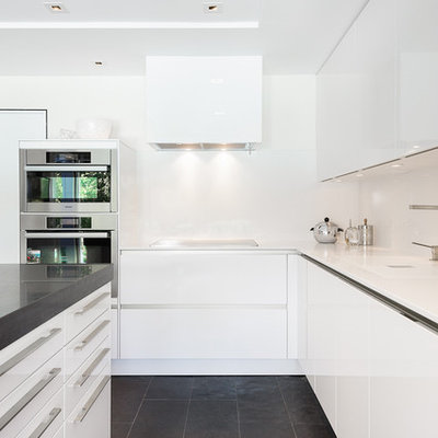 Mid-sized trendy l-shaped black floor and slate floor kitchen photo in Ottawa with flat-panel cabinets, white cabinets, quartzite countertops, white backsplash, stainless steel appliances and an island