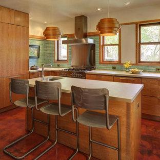 ミルウォーキーの中くらいのミッドセンチュリースタイルのおしゃれなキッチン (エプロンフロントシンク、フラットパネル扉のキャビネット、中間色木目調キャビネット、緑のキッチンパネル、セラミックタイルのキッチンパネル、シルバーの調理設備、人工大理石カウンター、クッションフロア、茶色い床) の写真