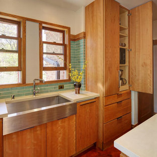 Photo of a mid-sized midcentury l-shaped eat-in kitchen in Milwaukee with a farmhouse sink, flat-panel cabinets, medium wood cabinets, green splashback, ceramic splashback, stainless steel appliances and with island.