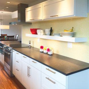他の地域の小さいミッドセンチュリースタイルのおしゃれなキッチン (アンダーカウンターシンク、シェーカースタイル扉のキャビネット、白いキャビネット、クオーツストーンカウンター、黄色いキッチンパネル、セラミックタイルのキッチンパネル、シルバーの調理設備、竹フローリング) の写真