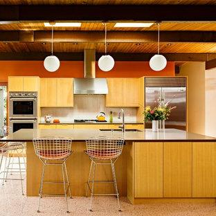 На фото: с высоким бюджетом параллельные кухни-гостиные среднего размера в стиле ретро с врезной раковиной, плоскими фасадами, фасадами цвета дерева среднего тона, столешницей из кварцевого композита, белым фартуком, фартуком из керамической плитки, техникой из нержавеющей стали и полом из терраццо
