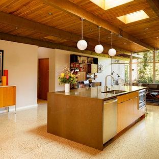 ポートランドの中サイズのミッドセンチュリースタイルのおしゃれなキッチン (アンダーカウンターシンク、フラットパネル扉のキャビネット、中間色木目調キャビネット、クオーツストーンカウンター、白いキッチンパネル、セラミックタイルのキッチンパネル、シルバーの調理設備の、テラゾの床) の写真