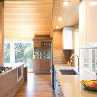 This is an example of a mid-sized midcentury u-shaped open plan kitchen in Seattle with a single-bowl sink, flat-panel cabinets, dark wood cabinets, quartz benchtops, mosaic tile splashback, stainless steel appliances, medium hardwood floors, with island, brown floor and white benchtop.