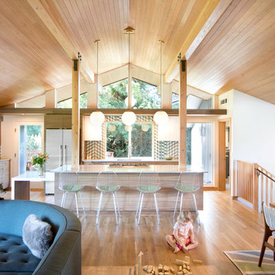 Example of a mid-sized 1950s l-shaped medium tone wood floor and brown floor open concept kitchen design in Seattle with an undermount sink, flat-panel cabinets, light wood cabinets, multicolored backsplash, stainless steel appliances, an island and white countertops