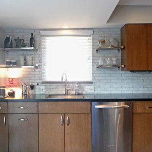 Mid-sized contemporary enclosed kitchen designs - Mid-sized trendy galley enclosed kitchen photo in Columbus with a single-bowl sink, flat-panel cabinets, medium tone wood cabinets, solid surface countertops, white backsplash, terra-cotta backsplash and stainless steel appliances