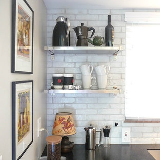 Design ideas for a mid-sized contemporary galley separate kitchen in Columbus with a single-bowl sink, flat-panel cabinets, medium wood cabinets, solid surface benchtops, white splashback, terra-cotta splashback, stainless steel appliances and linoleum floors.
