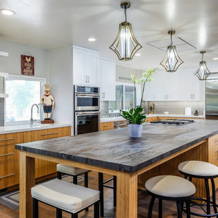 Large midcentury l-shaped eat-in kitchen in Sacramento with a farmhouse sink, flat-panel cabinets, medium wood cabinets, quartz benchtops, grey splashback, ceramic splashback, stainless steel appliances, medium hardwood floors, with island, brown floor and brown benchtop.