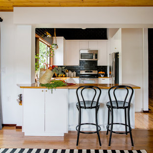 Photo of a midcentury u-shaped kitchen in Portland with a peninsula, flat-panel cabinets, white cabinets, wood benchtops, black splashback, subway tile splashback, stainless steel appliances and medium hardwood floors.