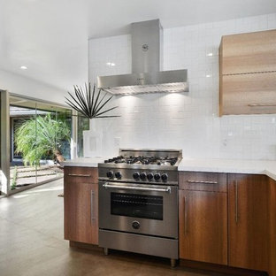 Inspiration for a mid-sized midcentury u-shaped eat-in kitchen in San Francisco with an undermount sink, flat-panel cabinets, medium wood cabinets, terrazzo benchtops, white splashback, ceramic splashback, stainless steel appliances, light hardwood floors, with island, grey floor and white benchtop.