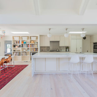 Design ideas for a midcentury open plan kitchen in San Francisco with an undermount sink, flat-panel cabinets, marble benchtops, panelled appliances, light hardwood floors, with island, white benchtop, beige cabinets, metallic splashback and beige floor.