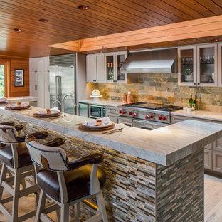 Klassisk inredning av ett mellanstort kök, med grå skåp, granitbänkskiva, rostfria vitvaror, ljust trägolv, en köksö, luckor med infälld panel, flerfärgad stänkskydd och stänkskydd i skiffer