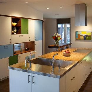 サンフランシスコの広いミッドセンチュリースタイルのおしゃれなキッチン (一体型シンク、フラットパネル扉のキャビネット、白いキャビネット、木材カウンター、白いキッチンパネル、ガラス板のキッチンパネル、シルバーの調理設備、無垢フローリング) の写真