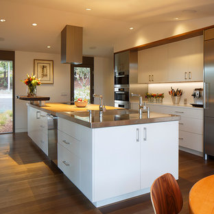 Large midcentury galley eat-in kitchen in San Francisco with flat-panel cabinets, white cabinets, wood benchtops, stainless steel appliances, with island, white splashback, glass sheet splashback, medium hardwood floors and an integrated sink.