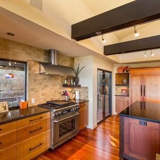 サクラメントの中サイズのアジアンスタイルのおしゃれなキッチン (御影石カウンター、ベージュキッチンパネル、セラミックタイルのキッチンパネル、無垢フローリング、茶色い床、アンダーカウンターシンク、シェーカースタイル扉のキャビネット、中間色木目調キャビネット、パネルと同色の調理設備) の写真