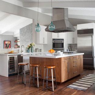 サンフランシスコの中サイズのコンテンポラリースタイルのおしゃれなキッチン (シルバーの調理設備の、フラットパネル扉のキャビネット、中間色木目調キャビネット、クオーツストーンカウンター、白いキッチンパネル、ガラスタイルのキッチンパネル、無垢フローリング) の写真