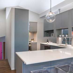 This is an example of a midcentury l-shaped eat-in kitchen in Boston with a single-bowl sink, flat-panel cabinets, grey cabinets, quartz benchtops, white splashback, mosaic tile splashback, stainless steel appliances, dark hardwood floors and a peninsula.