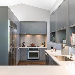 Inspiration för 60 tals kök, med en enkel diskho, släta luckor, grå skåp, bänkskiva i kvarts, vitt stänkskydd, stänkskydd i mosaik, rostfria vitvaror, mörkt trägolv och en halv köksö