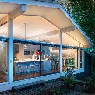 Midcentury l-shaped eat-in kitchen in Boston with a single-bowl sink, flat-panel cabinets, grey cabinets, quartz benchtops, stainless steel appliances, dark hardwood floors and a peninsula.