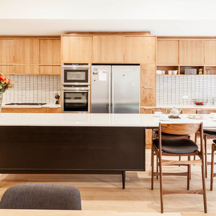 Photo of a large midcentury galley open plan kitchen in Melbourne with with island, quartz benchtops, an undermount sink, beige splashback, ceramic splashback, stainless steel appliances, flat-panel cabinets, light wood cabinets, light hardwood floors and beige floor.