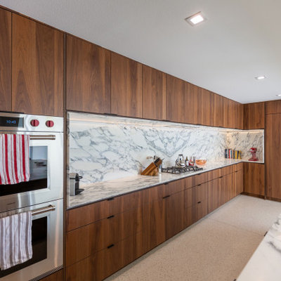 Example of a large 1950s single-wall terrazzo floor, white floor and exposed beam eat-in kitchen design in Other with an undermount sink, flat-panel cabinets, dark wood cabinets, quartz countertops, white backsplash, quartz backsplash, paneled appliances, a peninsula and white countertops