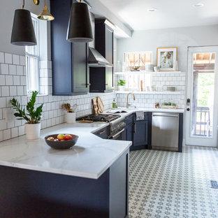 ワシントンD.C.の中くらいのミッドセンチュリースタイルのおしゃれなキッチン (アンダーカウンターシンク、シェーカースタイル扉のキャビネット、青いキャビネット、大理石カウンター、白いキッチンパネル、サブウェイタイルのキッチンパネル、シルバーの調理設備、クッションフロア、マルチカラーの床、白いキッチンカウンター) の写真