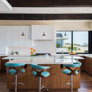 サンディエゴの中サイズのミッドセンチュリースタイルのおしゃれなキッチン (フラットパネル扉のキャビネット、クオーツストーンカウンター、ベージュキッチンパネル、パネルと同色の調理設備、無垢フローリング、ベージュのキッチンカウンター、ダブルシンク、中間色木目調キャビネット、茶色い床) の写真