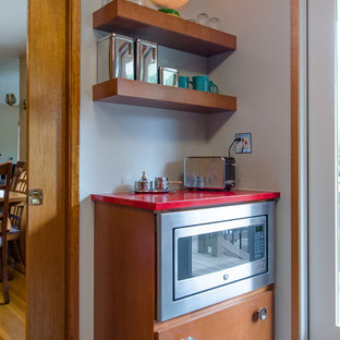 シアトルの中くらいのミッドセンチュリースタイルのおしゃれなキッチン (シングルシンク、フラットパネル扉のキャビネット、中間色木目調キャビネット、クオーツストーンカウンター、白いキッチンパネル、ガラスタイルのキッチンパネル、シルバーの調理設備、クッションフロア、アイランドなし、赤いキッチンカウンター) の写真