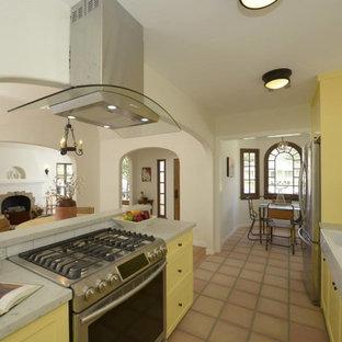 ロサンゼルスの中サイズのサンタフェスタイルのおしゃれなキッチン (ダブルシンク、シェーカースタイル扉のキャビネット、黄色いキャビネット、白いキッチンパネル、セラミックタイルのキッチンパネル、シルバーの調理設備の、テラコッタタイルの床、アイランドなし) の写真