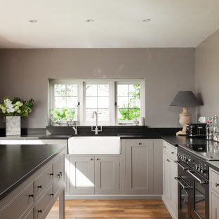 Kitchen - farmhouse kitchen idea in Kent with a farmhouse sink, gray cabinets and an island