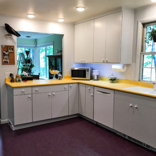 Inspiration for a mid-sized midcentury u-shaped separate kitchen in New York with an undermount sink, flat-panel cabinets, white cabinets, laminate benchtops, white splashback, white appliances, linoleum floors and purple floor.