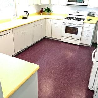 Geschlossene, Mittelgroße Mid-Century Küche in U-Form mit Unterbauwaschbecken, flächenbündigen Schrankfronten, weißen Schränken, Laminat-Arbeitsplatte, Küchenrückwand in Weiß, weißen Elektrogeräten, Linoleum und lila Boden in New York