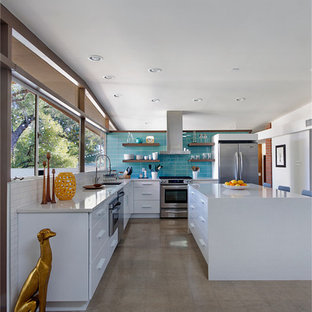 Photo of a mid-sized midcentury l-shaped eat-in kitchen in Phoenix with an undermount sink, flat-panel cabinets, white cabinets, quartz benchtops, blue splashback, glass tile splashback, stainless steel appliances, concrete floors and with island.