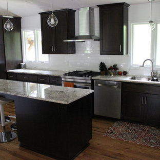 Photo of a large midcentury eat-in kitchen in Minneapolis with an undermount sink, flat-panel cabinets, dark wood cabinets, granite benchtops, white splashback, subway tile splashback, stainless steel appliances, light hardwood floors and with island.