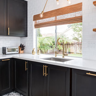 Mid-sized midcentury u-shaped separate kitchen in Los Angeles with an undermount sink, shaker cabinets, black cabinets, quartz benchtops, white splashback, subway tile splashback, porcelain floors, no island and white floor.