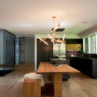 Contemporary eat-in kitchen remodeling - Example of a trendy u-shaped light wood floor eat-in kitchen design in Portland with black cabinets, concrete countertops, gray backsplash, glass tile backsplash, stainless steel appliances, an island and flat-panel cabinets