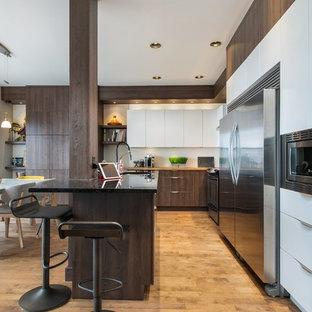 Foto di una cucina abitabile contemporanea di medie dimensioni con lavello sottopiano, ante lisce, elettrodomestici in acciaio inossidabile, isola, ante bianche, paraspruzzi bianco, pavimento in legno massello medio e top nero