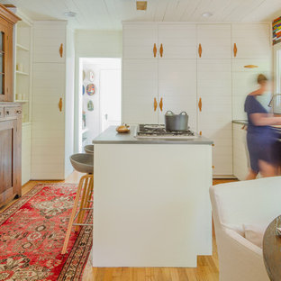 Mid-sized midcentury modern eat-in kitchen pictures - Inspiration for a mid-sized 1960s light wood floor eat-in kitchen remodel in Austin with white cabinets, concrete countertops, multicolored backsplash, glass tile backsplash and an island