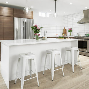 Design ideas for a mid-sized midcentury l-shaped separate kitchen in Toronto with a double-bowl sink, flat-panel cabinets, medium wood cabinets, quartzite benchtops, white splashback, ceramic splashback, stainless steel appliances, light hardwood floors, with island, beige floor and white benchtop.