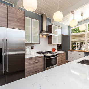 Inspiration for a small midcentury galley eat-in kitchen in Sacramento with an undermount sink, flat-panel cabinets, distressed cabinets, quartz benchtops, white splashback, ceramic splashback, stainless steel appliances and a peninsula.