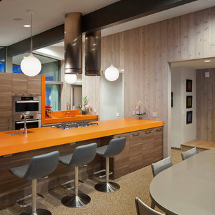 Midcentury galley eat-in kitchen in Austin with flat-panel cabinets, dark wood cabinets, stainless steel appliances, with island and orange benchtop.