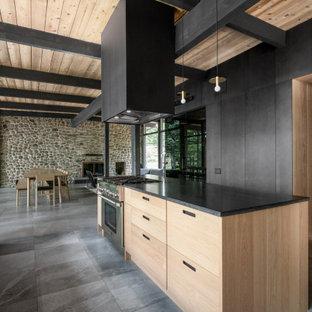 Идея дизайна: параллельная кухня в стиле ретро с плоскими фасадами, светлыми деревянными фасадами, островом, серым полом, черной столешницей и деревянным потолком