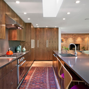 Photo of a mid-sized midcentury galley eat-in kitchen in Indianapolis with an undermount sink, flat-panel cabinets, medium wood cabinets, quartz benchtops, grey splashback, stone slab splashback, stainless steel appliances, light hardwood floors, with island and beige floor.