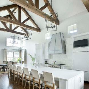 Foto di una cucina country con lavello sottopiano, ante in stile shaker, ante bianche, paraspruzzi bianco, paraspruzzi con piastrelle diamantate, parquet scuro, isola, pavimento marrone e top bianco