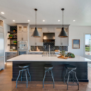 Large transitional u-shaped medium tone wood floor and brown floor eat-in kitchen photo in Boise with an undermount sink, shaker cabinets, gray cabinets, black backsplash, subway tile backsplash, stainless steel appliances, an island, white countertops and quartz countertops