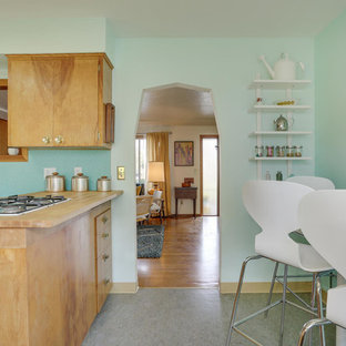 This is an example of a mid-sized midcentury u-shaped eat-in kitchen in Portland with a drop-in sink, flat-panel cabinets, light wood cabinets, laminate benchtops, blue splashback, white appliances, linoleum floors, a peninsula and turquoise floor.