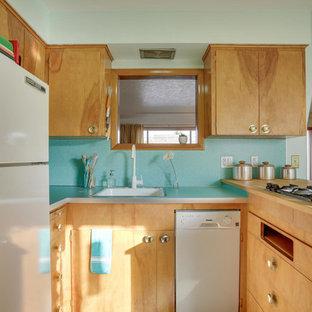 Idéer för mellanstora retro kök, med en nedsänkt diskho, släta luckor, skåp i ljust trä, laminatbänkskiva, blått stänkskydd, vita vitvaror, linoleumgolv, en halv köksö och turkost golv
