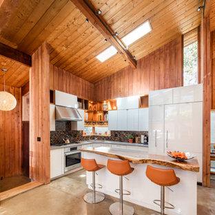 Retro Küche in L-Form mit Unterbauwaschbecken, flächenbündigen Schrankfronten, weißen Schränken, Küchenrückwand in Braun, Rückwand aus Mosaikfliesen, Elektrogeräten mit Frontblende, Betonboden, Kücheninsel, grauem Boden und grauer Arbeitsplatte in San Diego