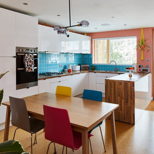 Inspiration for a retro u-shaped kitchen/diner in London with a single-bowl sink, flat-panel cabinets, white cabinets, wood worktops, blue splashback, cork flooring and a breakfast bar.